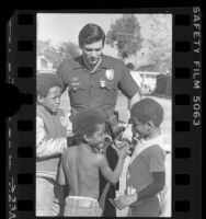 Three African American children mingling with police officer at Nickerson Gardens Housing Project in Los Angeles, Calif., 1985
