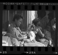 Rickie Gregory and daughter waiting along with other mothers for checkup at Watts Health Center in Los Angeles, Calif., 1985