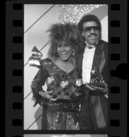 Singers Tina Turner and Lionel Richie posing with their Grammy Awards in Los Angeles, Calif., 1985