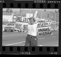 """Guardian Angels member with bilingual signs reading """"Gangs Out --Drugs Out"""" in Los Angeles, Calif., 1985"""