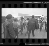 U.S. Immigration agents leading illegal aliens from Lights of America Company factory to buses in City of Industry, Calif., 1986