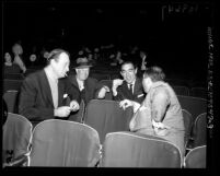 John Wayne, Maurice Chevalier, Anthony Quinn and Jerry Wald chatting in the empty seats of theater during 1958 Academy Awards rehearsals