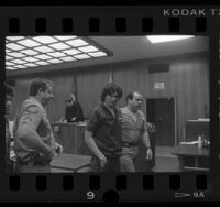 Richard Ramirez (aka The Night Stalker) smiling at camera as he is escorted by sheriffs from court in Los Angeles, Calif., 1986