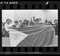 Filipinos holding flag of the Philippines during celebration of President Ferdinand E. Marcos' deposition Los Angeles, Calif., 1986