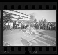 Anti-war demonstrators watching burning of napalm coated mannequin on Cal State Los Angeles campus, 1967