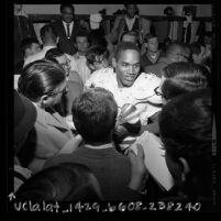 O.J. Simpson talking to reporters in locker-room after USC football game, 1967