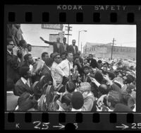 Congressman Adam Clayton Powell, surrounded by crowd and reporters during tour of Watts, Calif., 1968