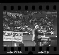 Dr. Benjamin Spock at podium during UCLA anti-war rally at Pauley Pavilion, 1968