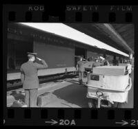 Escorts saluting caskets of Vietnam servicemen as they are unloaded from trains at Los Angeles Union Station, 1968