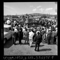 Crowd surrounding bulldozer, driven by Governor Ronald Regan, at groundbreaking for Harbor Freeway expansion, Los Angeles, 1968