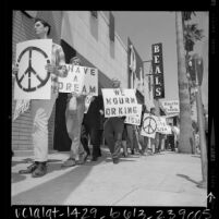 """Marchers with signs reading """"Have A Dream"""", """"We Mourn Dr King"""" and the peace symbol walking down sidewalk in Van Nuys, Calif., 1968"""