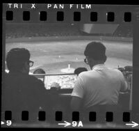 Los Angeles Dodgers game viewed over the shoulders of two reporters playing Scrabble, 1968