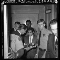 Sirhan Sirhan surrounded by sheriff deputies and lawyer Michael A. McCowan, Calif., 1969