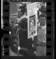 "Woman in crowd holding sign on which is written ""God Bless You Bobby…Rest In Peace"" surrounding a picture of Robert F. Kennedy, 1968"