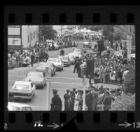 Procession of cars following hearse carrying body of Robert F. Kennedy driving down crowd lined street in Los Angeles, Calif., 1968