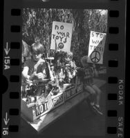 """Boy making sculpture from toy guns, as two children hold up signs stating """"Stop War Toys"""" in Los Angeles, Calif., 1968"""