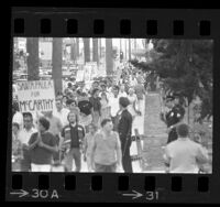 Pickets from the Peace Action Council protesting Hubert Humphrey visit, marching down sidewalk outside the Hollywood Palladium, 1968