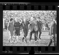 Nancy Reagan, Pat Nixon, Richard Nixon and Ronald Reagan walking across field at 1969 Rose Bowl game