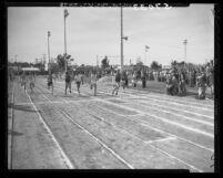 Collegiate 100-yard dash athletes cross finish line in Long Beach Relays, Calif., 1949