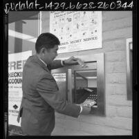 Mas Miyakoda, manager of Sumitomo Bank of California demonstrating how to use ATM machine in Monterey Park, Calif., 1969