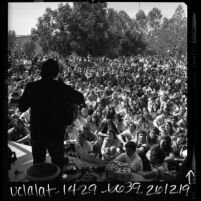 Silhouette of folk singer Phil Ochs on stage during Vietnam War moratorium event at Valley State College in Northridge, Calif., 1969
