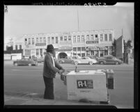 Street vendor gazing at old structure which will be torn down to make way for Hollywood Freeway, Los Angeles, 1949