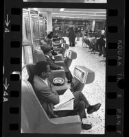 People watching individual coin-operated television sets at Greyhound Bus terminal in Los Angeles, Calif., 1969