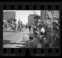 People, some with signs supporting President Richard Nixon, watching Veterans Day parade in Long Beach, Calif., 1969
