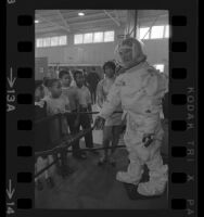 TRW Systems' employee showing school children model of Apollo astronauts' space suit at Space and Science Show in Los Angeles, Calif., 1969