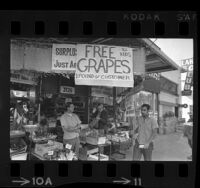 "Produce market offering free grapes while picket with sign stating ""Support Grape Boycott"" walks past in Los Angeles, Calif., 1969"
