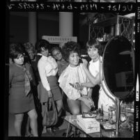 Flori Roberts Cosmetics makeup artist demonstrating products to women shoppers at May Co. store in Los Angeles, Calif., 1970