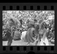 Four women dancing amongst crowd at an Easter Love In held at Elysian Park, Los Angeles, 1970