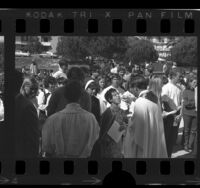 Loyola University president Reverend Donald P. Merrifield holding communion for anti-war marchers, Calif., 1970