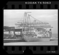 Cranes loading freight containers onto the cargo ship Kauai in the Port of Los Angeles, Calif., 1986
