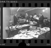 Police investigators displaying guns, office equipment and credit cards recovered in sting operation in Los Angeles, Calif., 1986