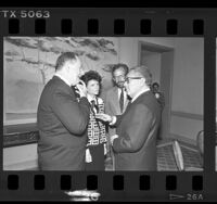 Henry Kissinger speaking with Peter Gold, Constance Austin, and Frank Ellsworth in Los Angeles, Calif., 1986