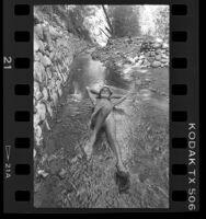 "Robert ""Gypsy Boots"" Bootzin laying in a stream, Los Angeles, Calif., 1986"