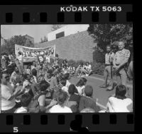 "UCLA students in sit-down protest with banner reading ""UC Out of South Africa! Divest Now"" as two UC Police officers watch Los Angeles, Calif., 1986"