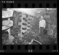 Deputy Fire Chief Don Anthony amongst stacks destroyed by fire at Los Angeles Central Library, 1986
