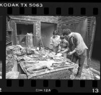 Joaquin Coronel, Luis Flores and Juan Villa sorting belongs in burned out apartment in Los Angeles, Calif., 1986