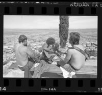 Three inmates playing guitars and harmonica on hilltop overlooking the desert at Boron Federal Prison, Calif., 1986