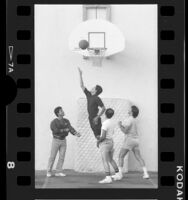 Four men playing basketball in Union Rescue Mission league in Los Angeles, Calif., 1986