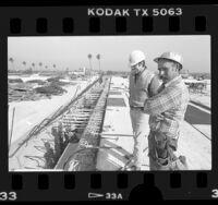 Cal Trans workers Ken Burkle and Steve Winegar watching work on a hinge closure on the Century Freeway, 1986