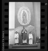 Father Luis Olivares standing below Virgin of Guadalupe icon, Los Angeles, Calif., 1986