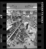 Worker cleaning up Vons store after earthquake in Desert Hot Springs, Calif., 1986