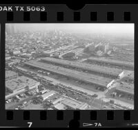 Aerial view of Los Angeles Wholesale Produce Market on Central Avenue and downtown skyline, 1986