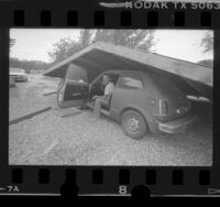Dean Walters and car under collapsed carport after Chalfant earthquake, Calif., 1986