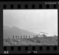 Helicopter and fire crew on ridge of mountain in Angeles National Forest, Calif., 1986