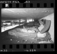 Illegal immigrant squatter on mattress under freeway in Los Angeles, Calif., 1986