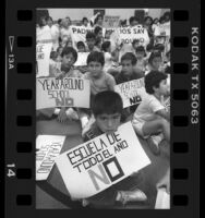 "Parents and children with bilingual signs reading ""Year Around School No"" in Los Angeles, Calif., 1986"